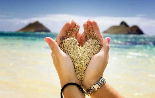 mãos segurando areia em forma de coração