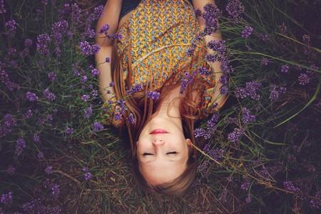 menina deitada entre flores de Lavanda respirando a paz