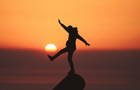 jovem ao poente, sobre um rochedo, com o pé parecendo chutar o próprio sol, como uma bola