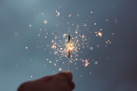 mão que segura mini fogo de artifício contra fundo nocturno