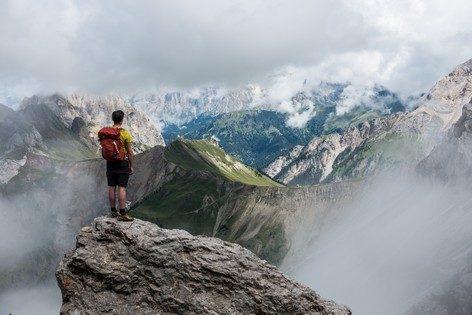 Jovem escalador no alto de montanha rodeado de nuvens e píncaros