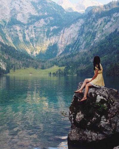 jovem sentada num rochedo alto contemplando um lago rodeado de altas montanhas