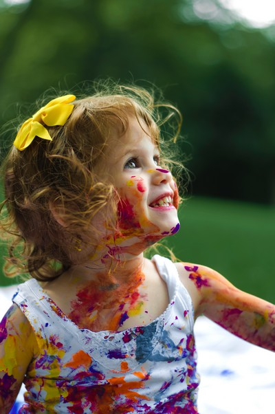 menina salpicada de tintas coloridas sorrindo