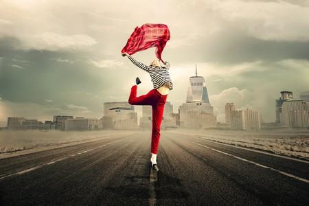 jovem a saltar na rua com calças encarnadas e segurando um tecido igual sobre a cabeça com os braços estendidos