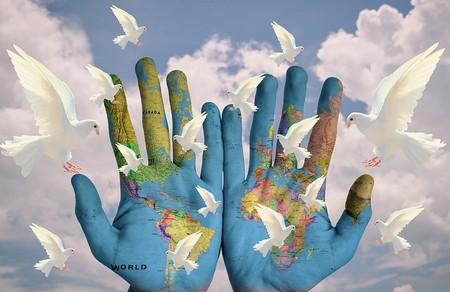duas palmas das mãos onde está pintado o mundo, rodeadas de pombas