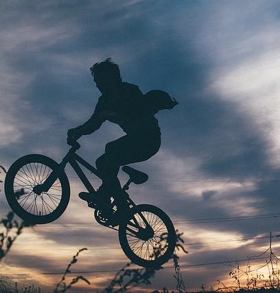 silhueta de ciclista que parece voar contra um céu de tempestade