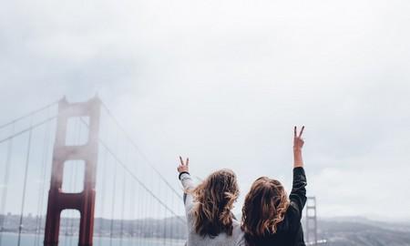 duas jovens de costas, apontando para o horizonte