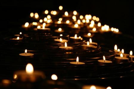 multidão de velas acesas contra fundo escuro