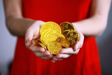 mãos de jovem a oferecer moedas de ouro em chocolate
