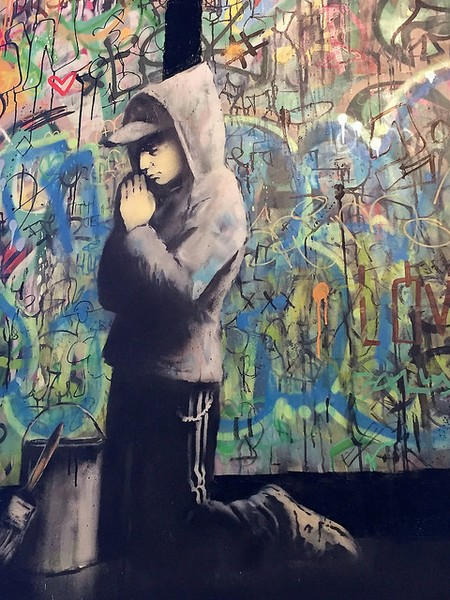 figura de Bansky ajoelhado na rua contra um mural de cruzes sugeridas