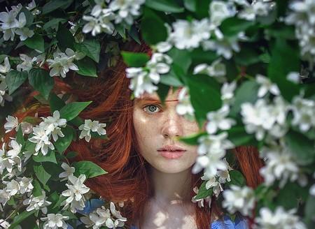 jovem entre flores brancas e folhas verdes