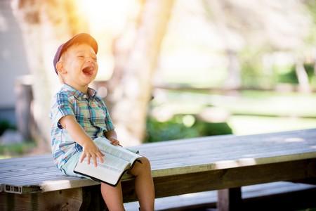 menino rindo sentado num banco com um livro no colo