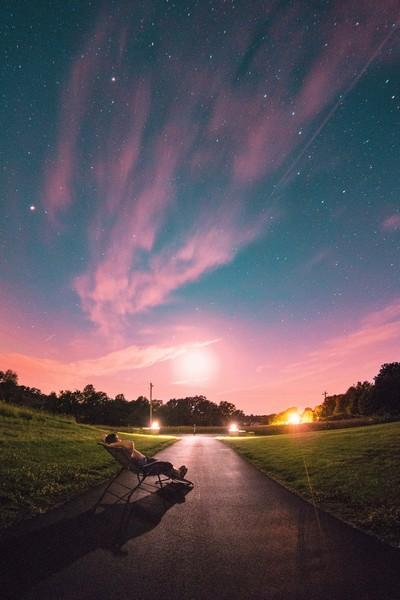 homem recostado numa espreguiçadeira contemplando o céu estrelado ao amanhecer
