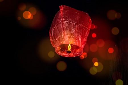 balões iluminados por tochas ardentes, sem os queimar, contra o fundo escuro do céu