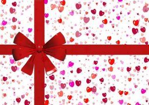 presente com papel de corações e laço vermelho