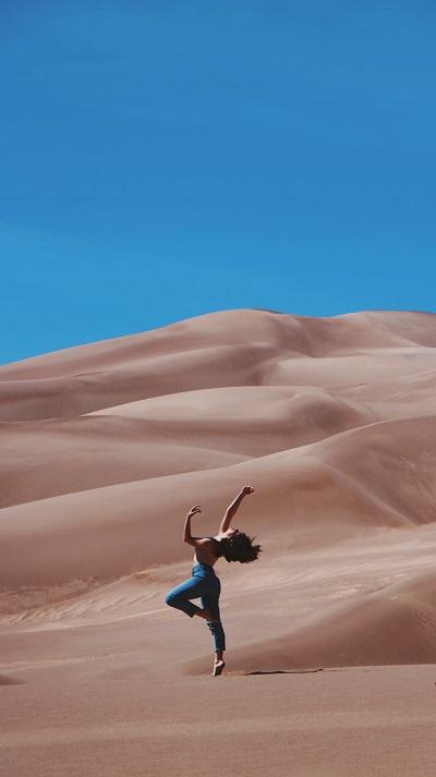 jovem exultante entre dunas no deserto sob um céu azul