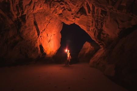 rapaz explorando caverna imensa com uma simples tocha