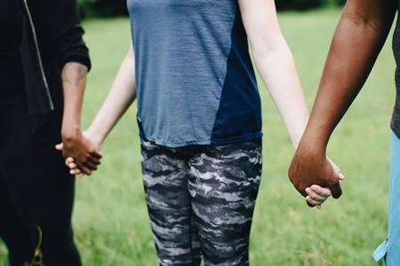 criança branca dando as mãos a crianças de cor