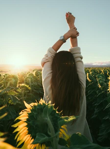 jovem de costas, num campo de girassóis iluminado, com os braços erguidos e um relógio no pulso