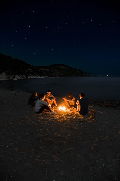 jovens na praia à noite, em volta de uma fogueira, sob estrelas