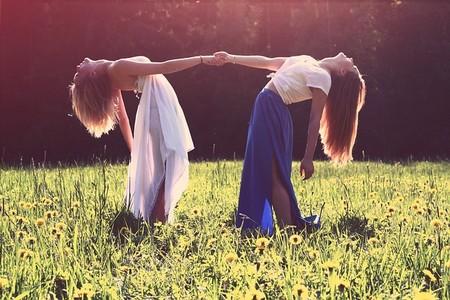 duas jovens dão as mãos e inclinam-se para trás segurando-se mutuamente