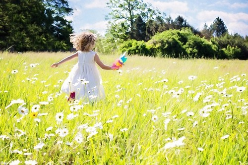 menina correndo no prado