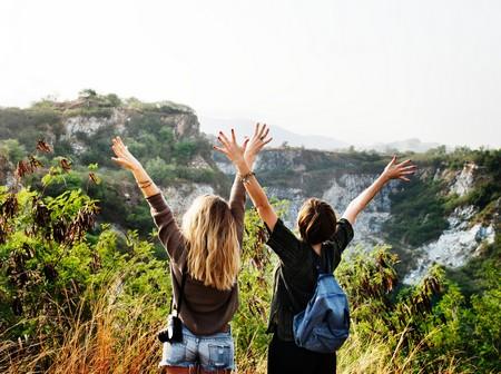 duas amigas de costas, numa paisagem campestre com os braços erguidos
