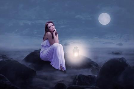 jovem ao luar, sentada, com vestido branco