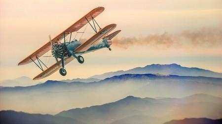 avião pequenino e muito antigo sobre as nuvens e as montanhas ao poente