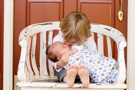 menino com seu irmão bebé ao colo