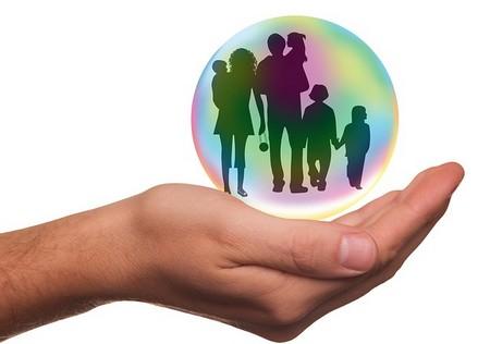 mão aberta segurando bola transparente com família dentro