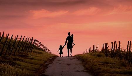 Mãe sem abrigo caminhando com dois filhos ao por do sol
