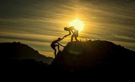 ajuda a subir rochedo contra fundo de poente