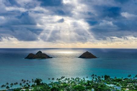 luz entre nuvens sobre o mar entre dois rochedos
