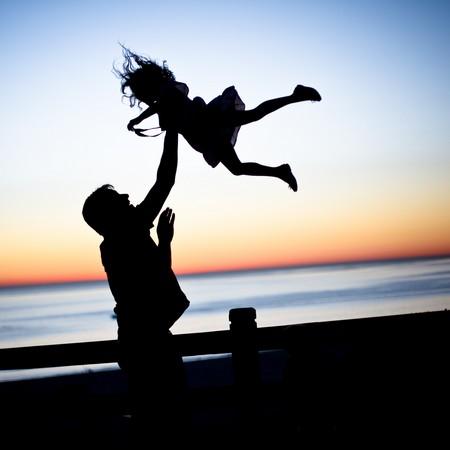 pai que atira a filha ao ar contra fundo de poente